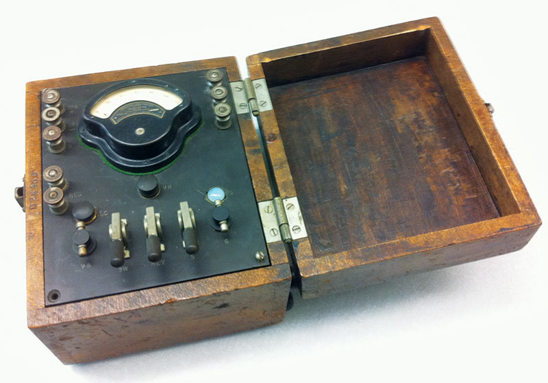 Antique test meter from an instrument collection at MIT, acquired by the school in the 1940s. The top center instrument is a miniature Weston voltmeter whose scale ranges from 0 to 120. The shape of the voltmeter is reflected in Sigma Pi Sigma's insignia.