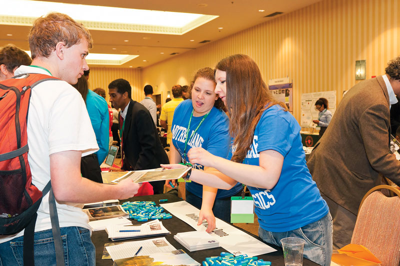 Sarah Reiff and Sylwia Ptasinska from the University of Notre Dame speak with a student in the Exhibit Hall.
