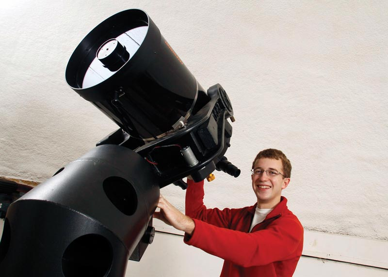 Josh Fuchs poses with the telescope at Rhodes College that he used in public outreach projects. Photo courtesy of Josh Fuchs.