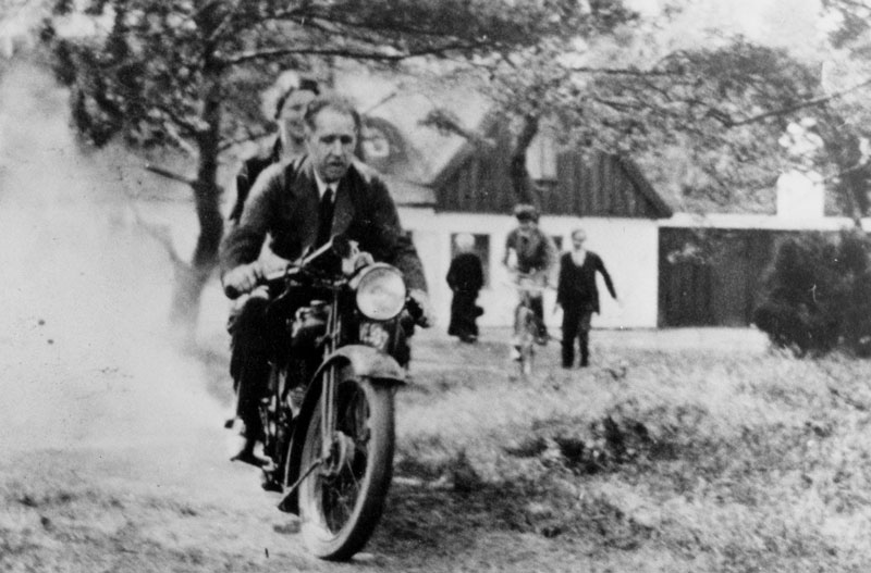 Niels Bohr and his wife Margrethe ride George Gamow's motorcycle at their summer home in Tisvilde, Denmark.