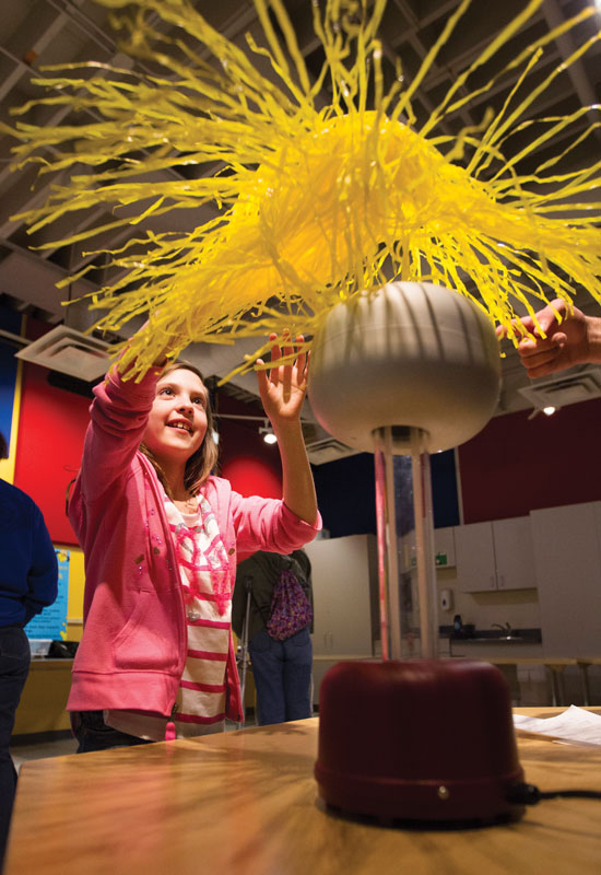 A young girl explores the wonder of static electricity with a Van de Graaff generator.