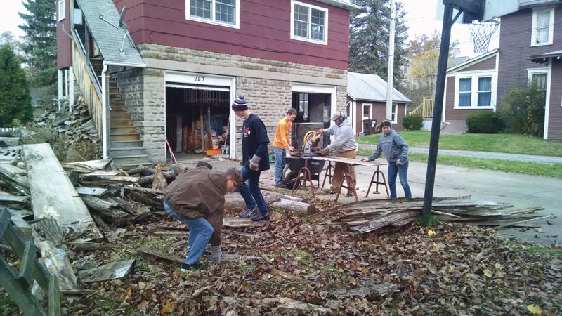 Seth Byard, Dan Seiter, Connor Murphy, and Mercedes Mansfield) help professor Michael Coulter (on the saw) sort and prepare wood for his furnace as part of our Rent-a-Student campaign in 2015. Photo by author.