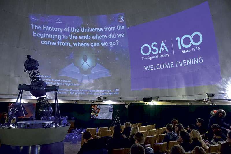 "Attendees await the live broadcast of Nobel winner Prof. John C. Mather's presentation at the ""OSA Welcome Evening."" The event was hosted by the OSA student chapter of Vilnius University at the university's planetarium. Photo courtesy of The Optical Society."