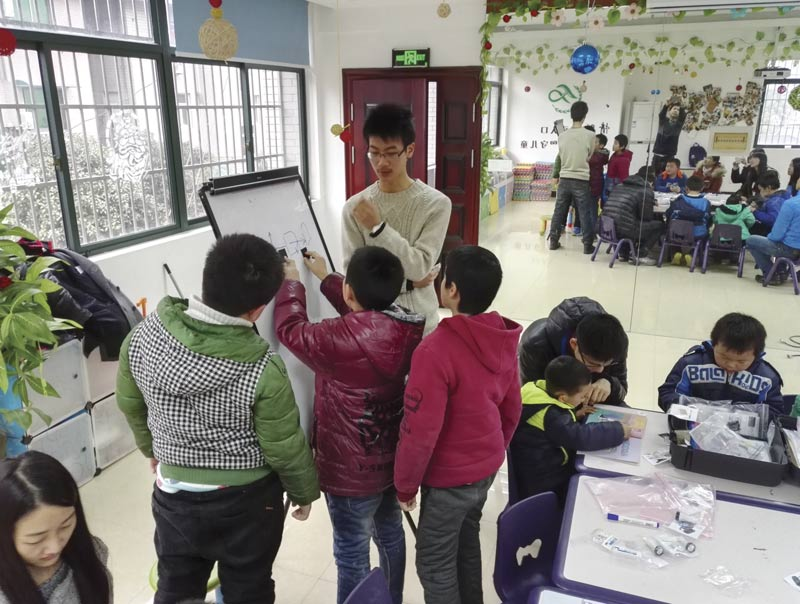 A member of the OSA student chapter at Zhejiang University works with children from Youth Homes in Hangzhou on activities from the Optics Suitcase. Photo courtesy of The Optical Society.