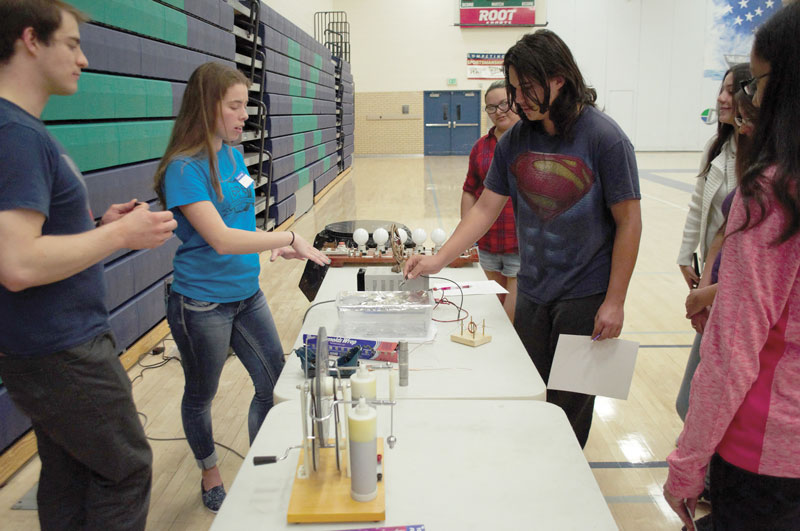 acob Wikowsky and Lindsey Hart show a student the mini-plasma cutter made from a voltage supply, pencil lead, and aluminum foil. Photo by Allison Tucker.