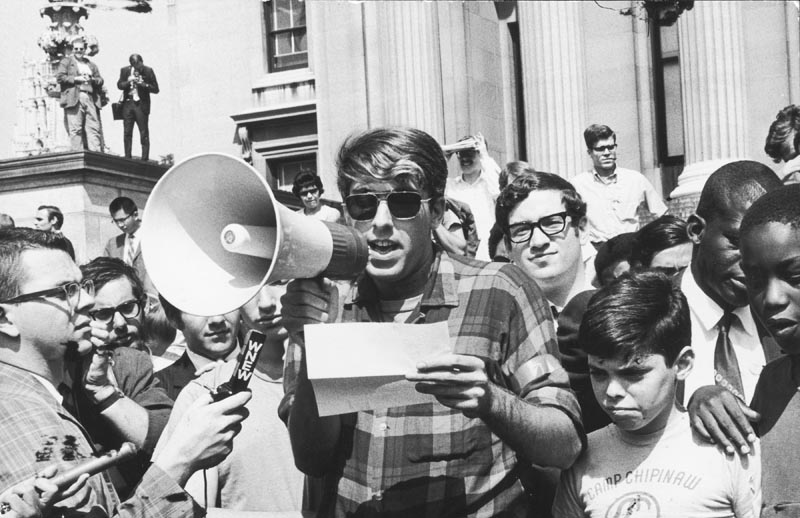 During the height of the 1968 protests at Columbia University, American political activist Mark Rudd, a leader of Students for a Democratic Society (SDS), reads the organization's 'Student Demands to School Administration' through a bullhorn to assembled students and journalists, New York, New York, September 20, 1968. Photo by Fred W. McDarrah/Getty Images.