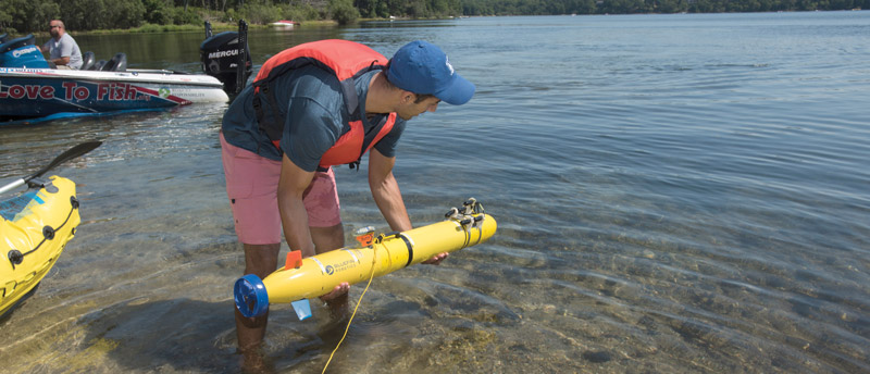 Bhatt testing an autonomous underwater vehicle at Ashumet Pond in East Falmouth, Massachusetts. Photo by Tom Kleindinst. © Woods Hole Oceanographic Institution.