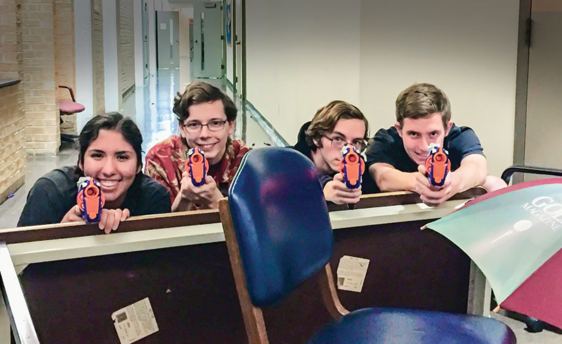 Members of the University of Dallas SPS chapter hiding behind an obstacle made of an overturned table and chair. Photo by Tessa Rosenberger.