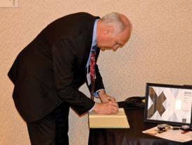 "AIP CEO Robert G.W. Brown signing the ""Red Book"" after being inducted into Sigma Pi Sigma. Photo by Matt Payne."
