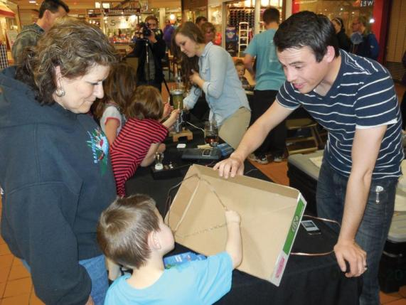 Idaho State University students Justin Anderson  (foreground with the box speaker) and Alexis Chlarson (with the jumping ring demo) engage shoppers at a local mall during an SPS outreach event. Photo courtesy of Steve Shropshire.
