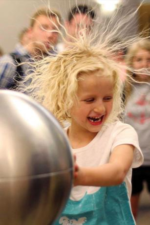 Audience member Payton Martin has a hair-raising experience with a Van de Graaff generator. Photo courtesy of Ben Pound.