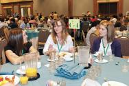 Workshop leader Shelly Arnold (center) visits with students over breakfast at PhysCon 2012.